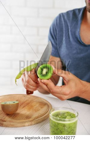 Young man peeling kiwi, preparing orange juice