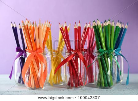 Bright pencils in glass jars on wooden table, on purple background