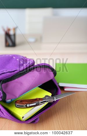 Backpack with knife in classroom, close up. Juvenile delinquency