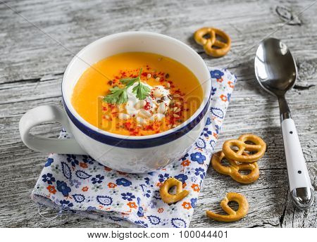 Pumpkin Soup With Paprika And Cream And Crackers On A Light Wooden Surface