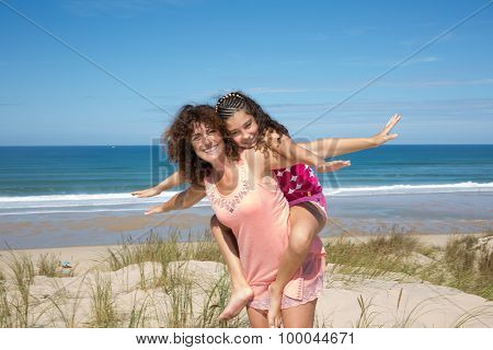 Lovely Picture Of A Mother With Her Daughter Giving A Piggy Back