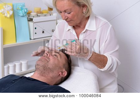 Female Doctor Giving Injection To Patient