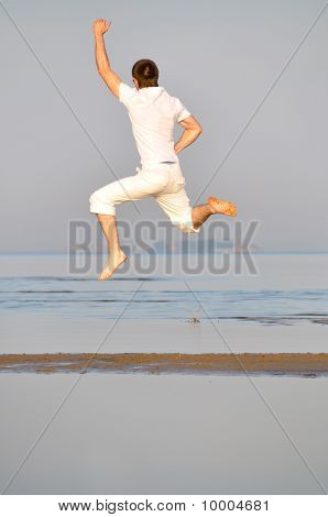 Man In White Dress Is Jumping On The Morning Beach