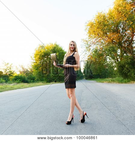 Young Beautiful Slender Girl With A Laptop On The Road