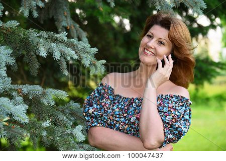 Woman talking on cell phone in the park