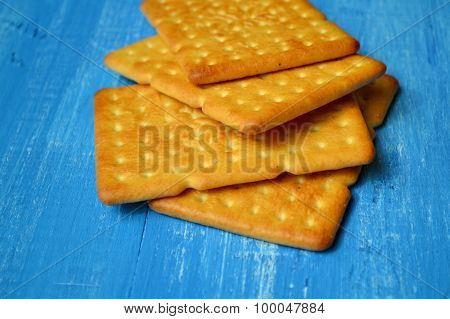 Tasty salty crackers on blue wooden background