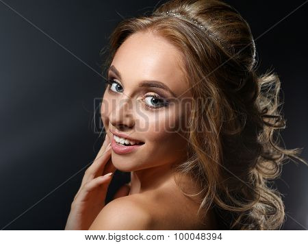 Beautiful woman with curly long hair on dark background