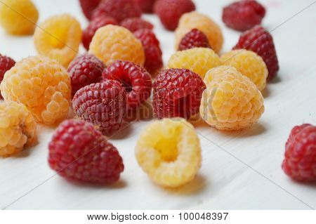 Bright pink and yellow raspberries on white wooden board