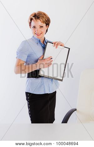 Lovely woman standing nearby desk