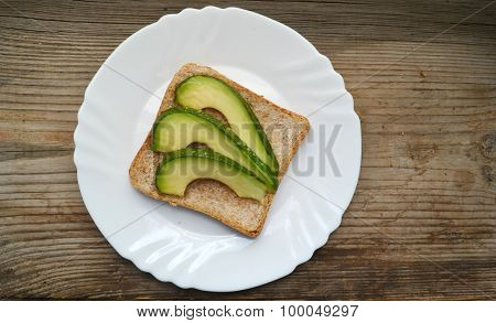 Healthy green avocado sandwich on white plate placed on wooden table