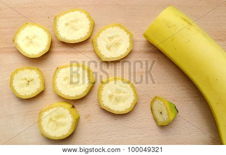 Yellow banana slices on wooden board