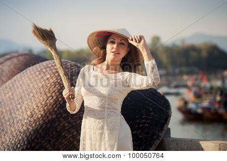 Blonde Girl In Vietnamese Dress Holds Besom On Embankment