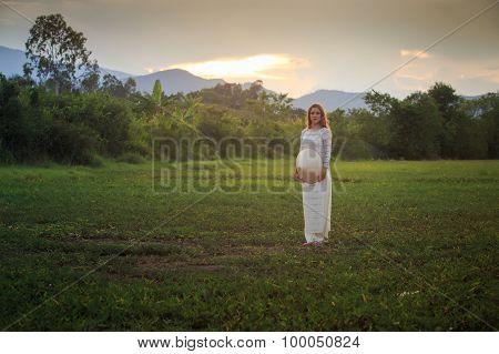 Blonde Girl In Vietnamese Dress Holds Hat On Field