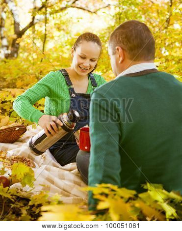 Pregnant Couple Having Picnic In Autumn Park