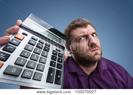Upset man with calculator