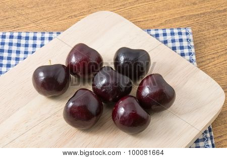 Group Of Red Plums On Wooden Cutting Board