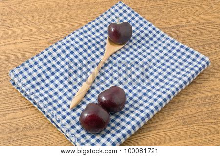 Red Plums On A Blue Checked Napkin