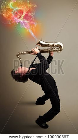 Attractive young musician playing on saxophone with colorful abstract fume comming out poster