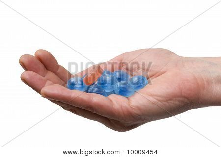 blue candies in a hand isolated on white background