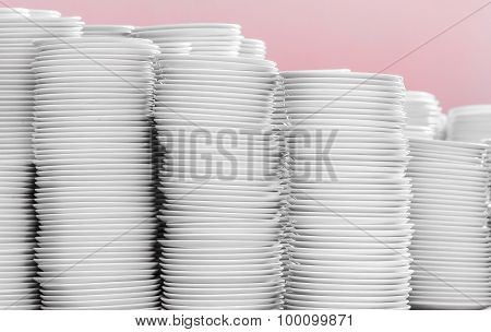 Stack of white plates on pink background.