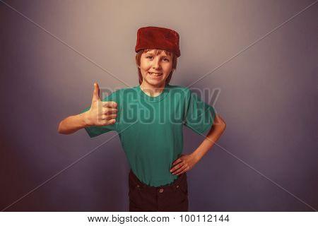 Muslim boy of ten years, skullcap, thumbs up on a gray backgroun