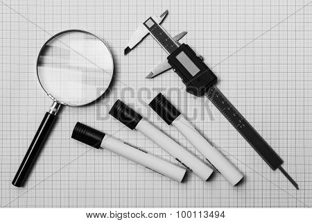 Magnifying Glass, Slide Calliper And Pens On A Graph Paper