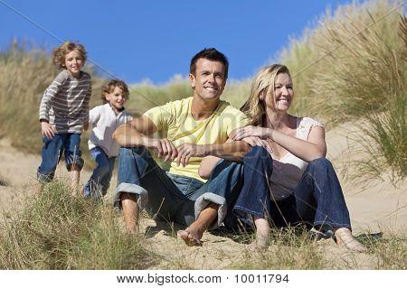 Family Sitting On Beach Having Fun
