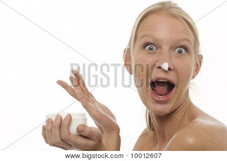 portrait of a young caucasian woman with open mouth who plays with the moisturizing cream on the nos