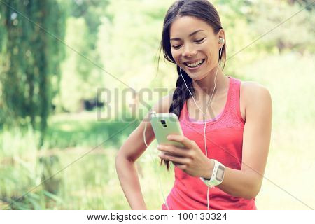 Happy young fit woman using cell phone while listening to music on smartphone. Smiling mixed race Asian / Caucasian female is in sports clothing. She is enjoying music in park.