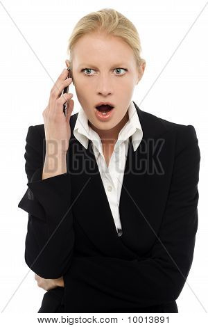 portrait of a young caucasian businesswoman talking on the phone with aggressive air