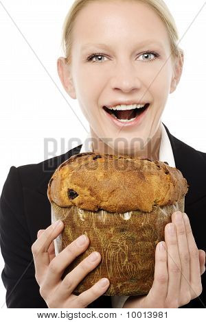 portrait of a young caucasian businesswoman smiling and holding a panettone