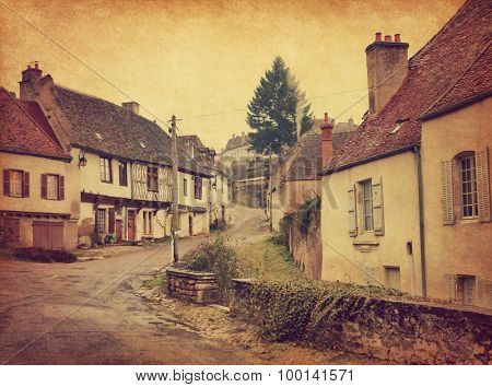 Winding street with old houses in Semur-en-Auxois,  Burgundy, France. Photo in retro style. Paper texture.