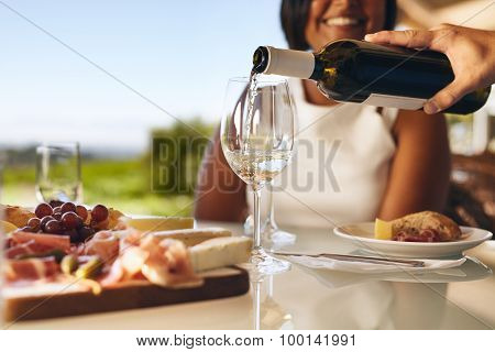 Human Hand Pouring White Wine From A Bottle