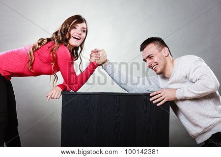 Partnership relationship concept. Girlfriend confronts his boyfriend. Woman and man arm wrestling challenge between young couple poster