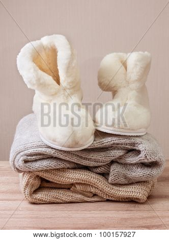 Pair of warm winter sheepskin slippers (alpaca) on pile of warm woolen clothes (Selective focus) poster