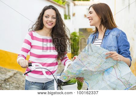 Two beautiful female tourists searching a place on the map poster