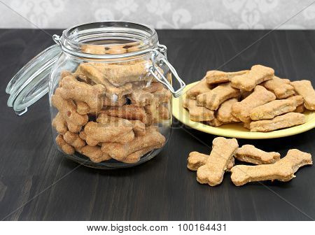 Dog Bones In A Canister And On A Wooden Counter.  Healthy Homeade Treats For A Dog.