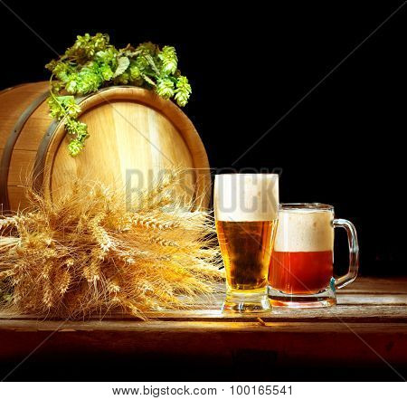 Beer. Vintage barrel and glasses full of fresh beer with hop cones and wheat of ears on wooden table isolated over black background. Brewing traditions. Ingredients for beer. Brewery concept