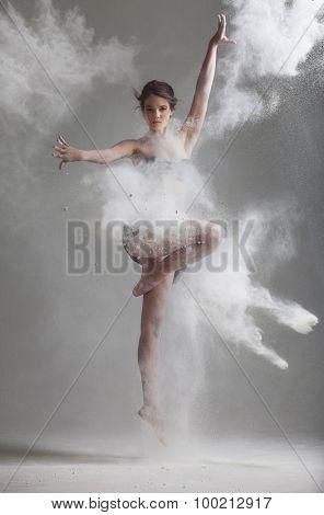 Studio portrait of woman dancing with flour