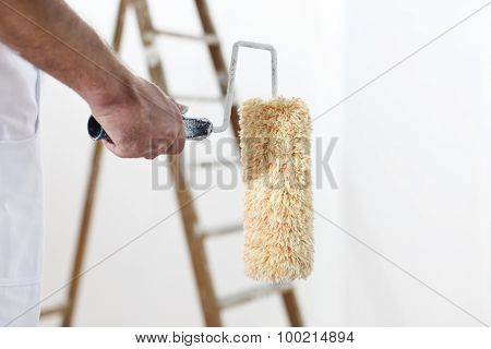 Painter Man At Work With A Paint Roller And Ladder, Hand Clsose Up