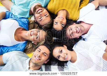 Group of cheerful friends lying together in a circle