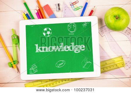 The word knowledge and school doodles against students desk with tablet pc