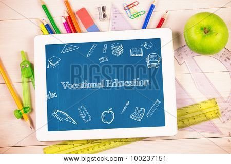 The word vocational education and education doodles against students desk with tablet pc