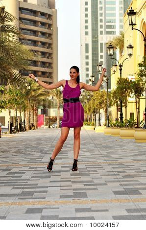Young Beautiful Woman In Purple Dress Posing On The Street