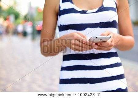 Midsection of young woman texting on smartphone on street. She is holding mobile cell phone while walking on road in city. Front view of female is in striped clothing.