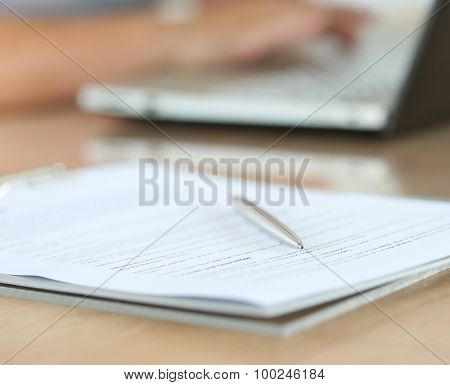 Silver Pen Lying On Document Pad