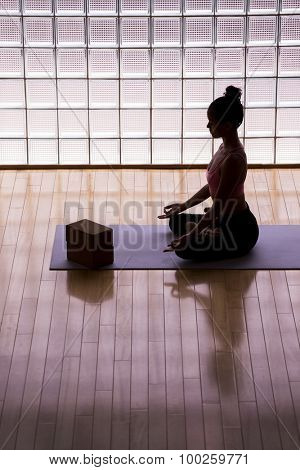 Young woman practicing meditation in a yoga studio indoors.