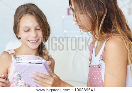 Mother helps her preteen daugher learning ipad together poster