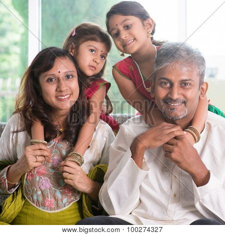 Happy Indian family at home. Asian parents piggyback their children. Adults and kids indoor lifestyle.