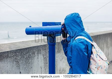 A person wearing a blue jacket and hood is using a telescope on the coast poster